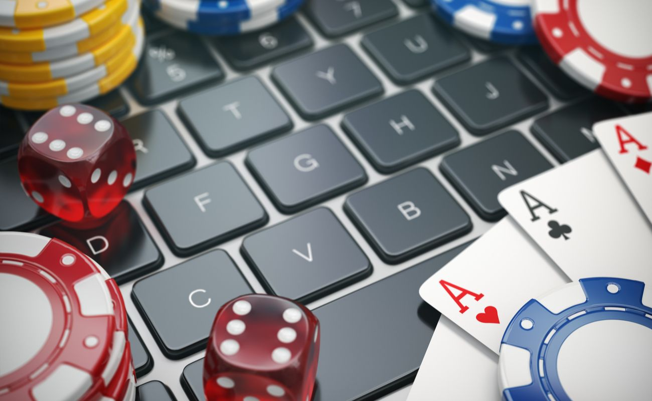 Gambling chips cards and dice on laptop computer keyboard background