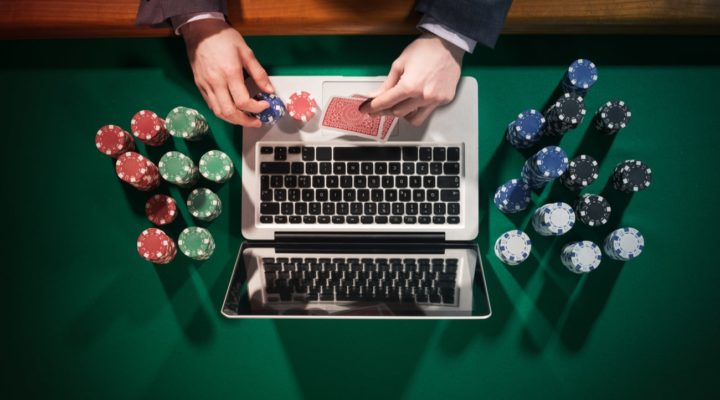 Top view of a man playing online poker with laptop on a green table with poker chips all around
