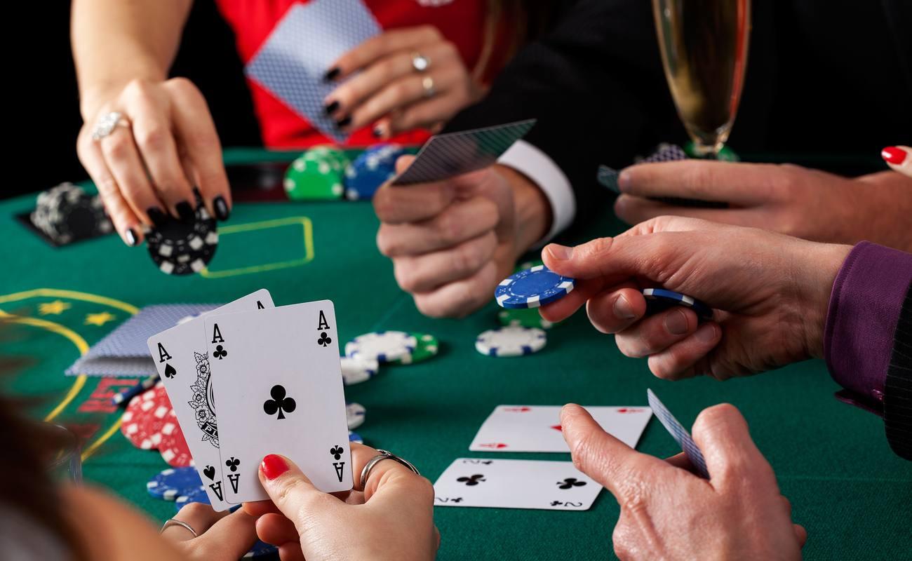 tangan di meja poker memegang chip poker dan kartu