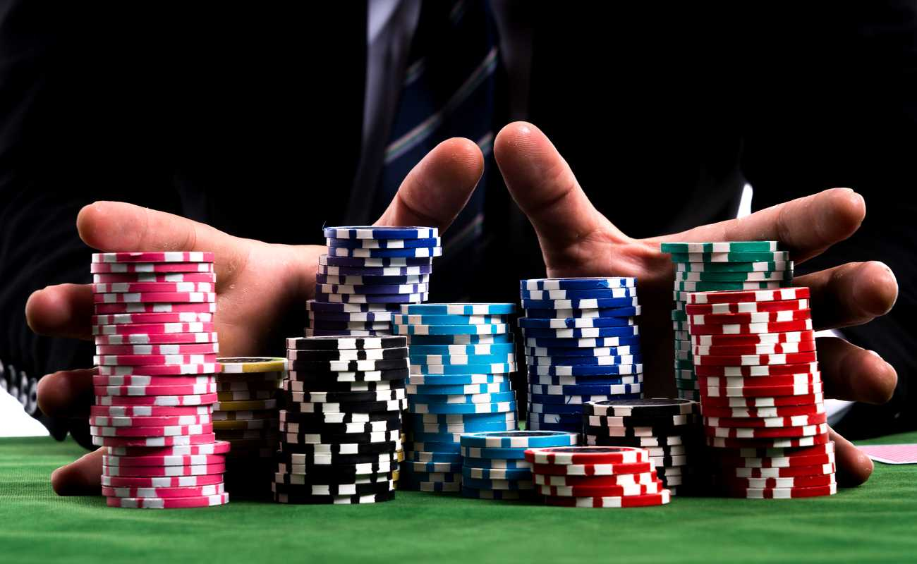 Close up of hands pushing large stack of colored poker chips across gaming table for betting
