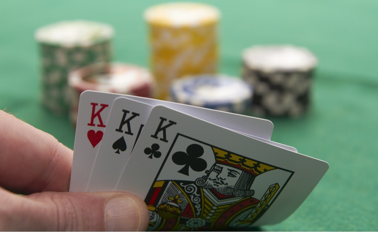 Poker hand showing three kings with poker chips in the background