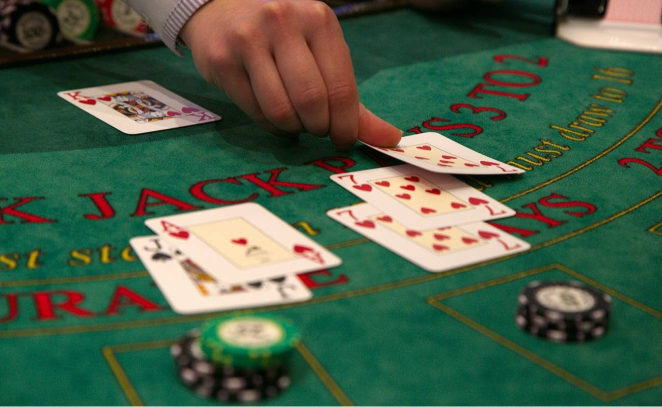 Closeup of a dealer putting down a card on a blackjack table