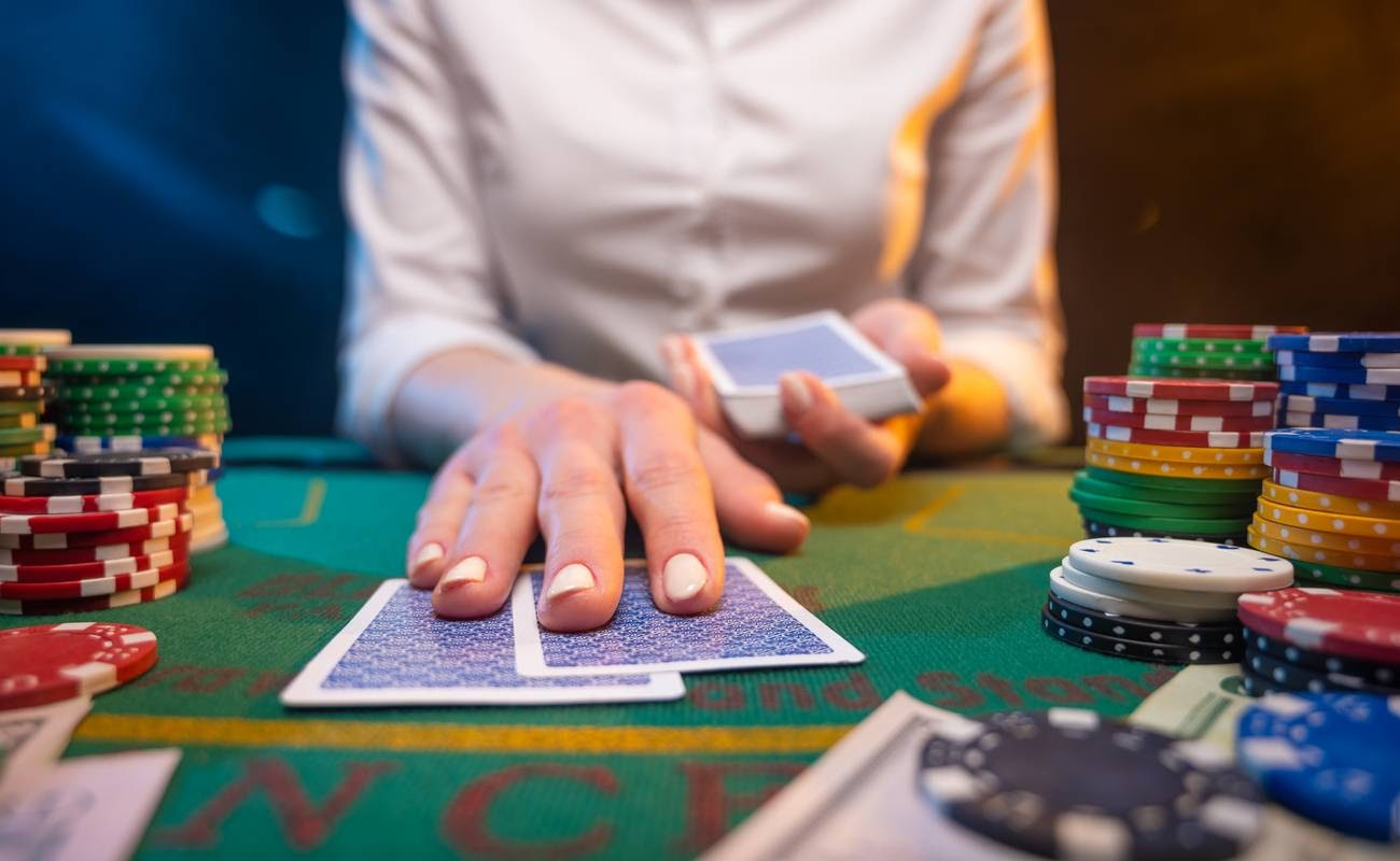 Close up of woman's hand pushing playing cards forward on a table surrounded casino chips