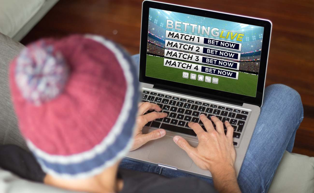 Man with laptop on his legs placing live bets