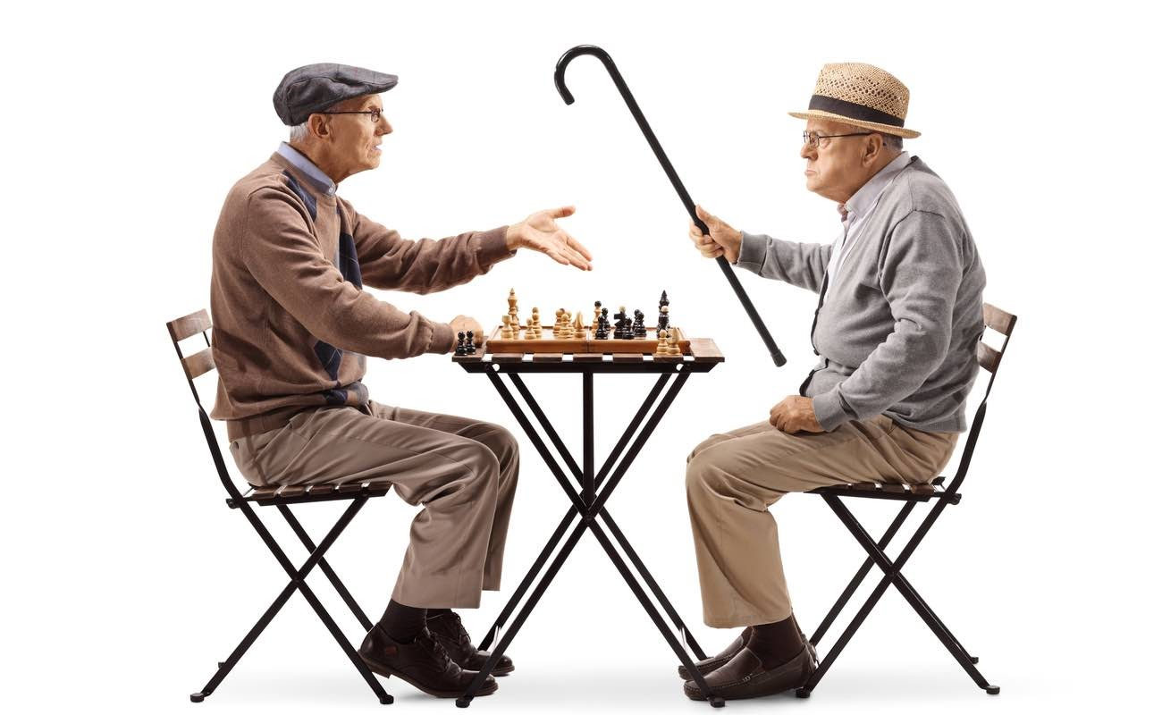 Seniors playing a game of chess and arguing isolated on white background