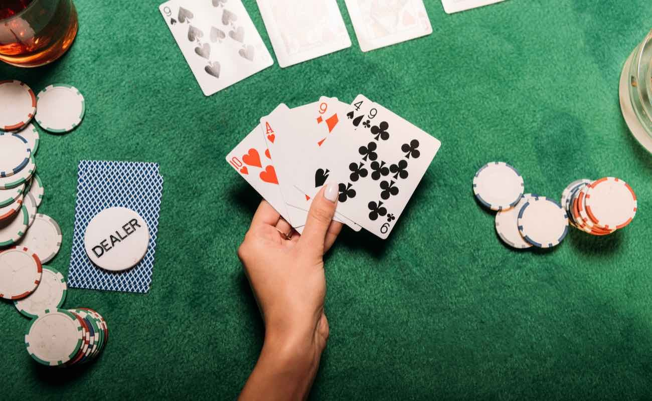 Cropped image of woman playing poker at table in casino and holding playing cards