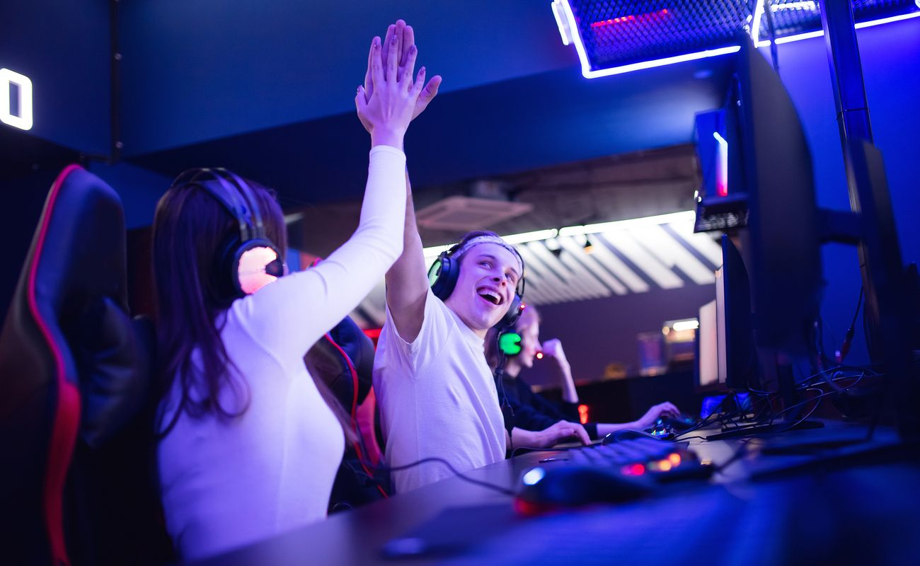 Two gamers high-five each other after winning a game online