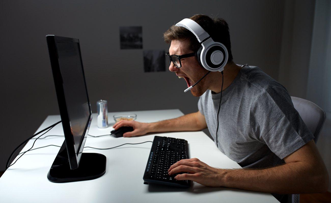 Seorang pemain PC yang memakai headset dengan mikrofon berteriak di layar.