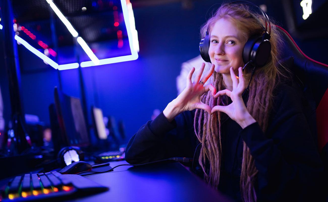 Seorang gamer yang memakai headphone membuat simbol hati dengan jari-jarinya saat duduk di depan PC-nya.