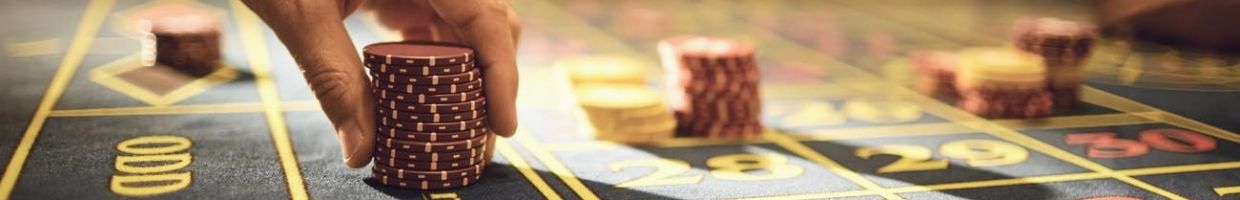 Closeup of a person holding casino chips at a roulette table