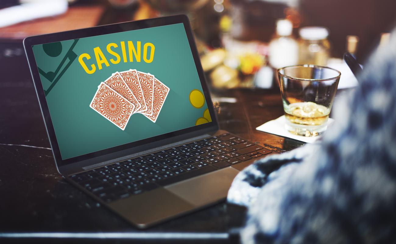 Seseorang memainkan permainan kasino online sambil menikmati minuman