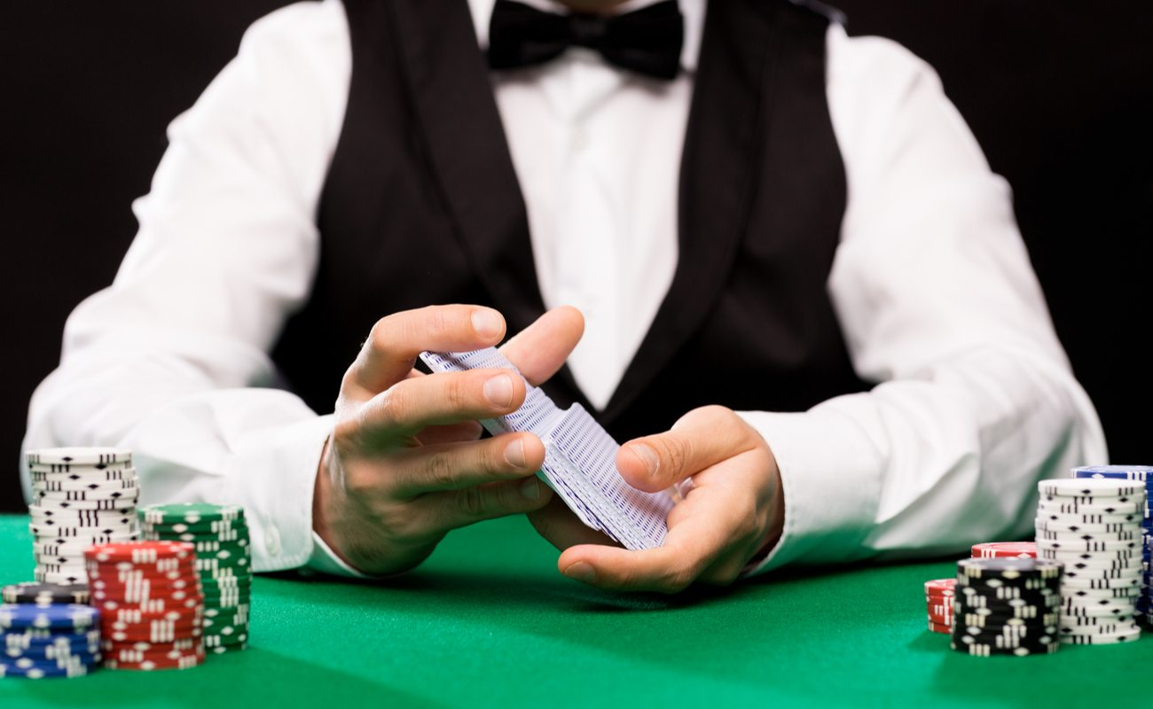 A casino dealer shuffles cards with piles of chips on the table in front of them