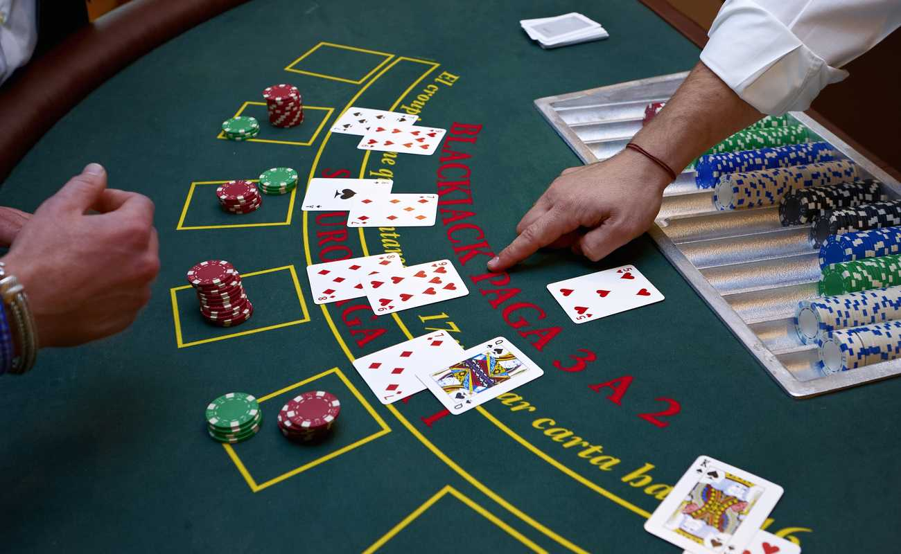 Dealer pointing to a spot on a blackjack casino games table.
