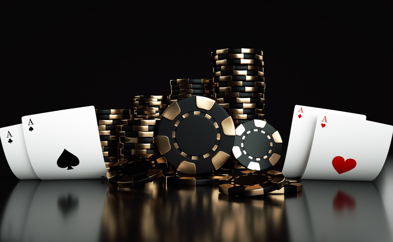 Stacks of black and gold chips flanked by pairs of Aces on either side.