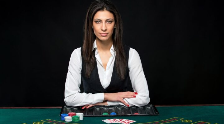 A female casino dealer is ready to start a game.