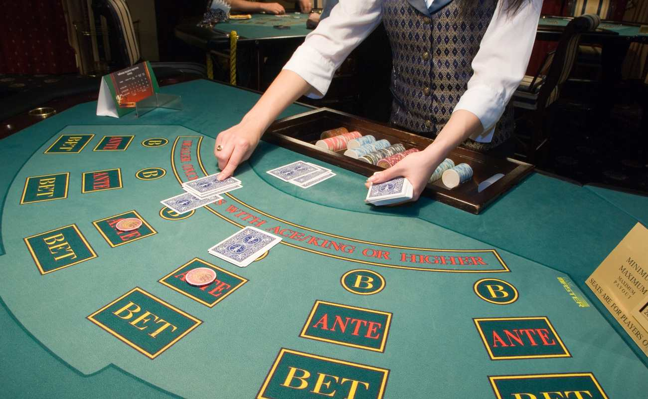 A dealer places cards on a casino game table.