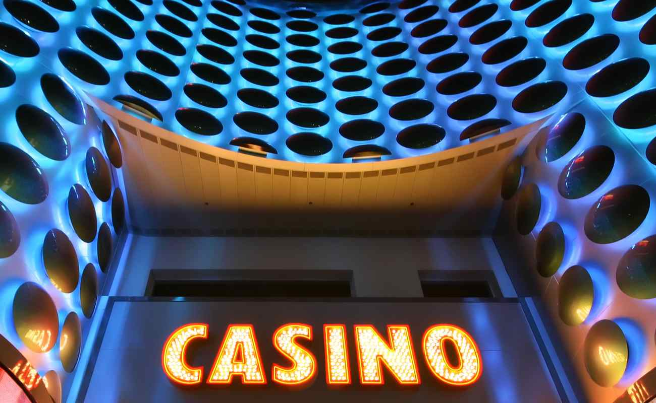 A bright casino sign in lights on the side of a building.