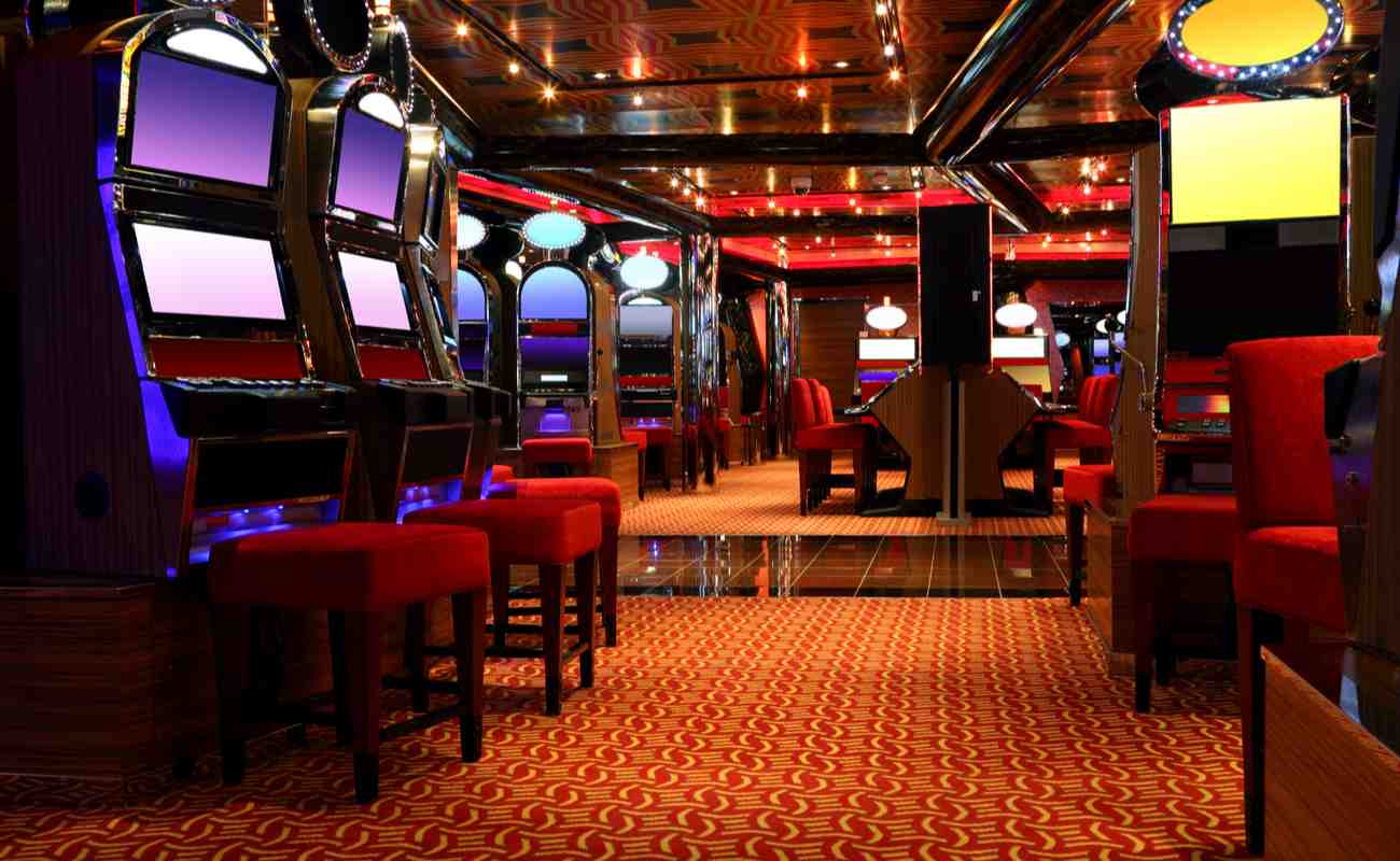 An empty casino with vacant machines and chairs.