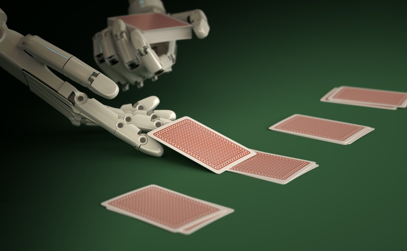 A robot deals out cards onto a green table.