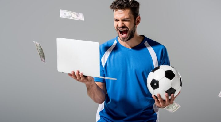 A sports fan holding a laptop and a soccer ball while money falls around him.