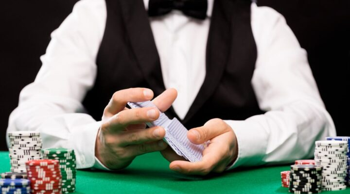 Casino dealer shuffles playing cards at a green felt table with chip stacks.