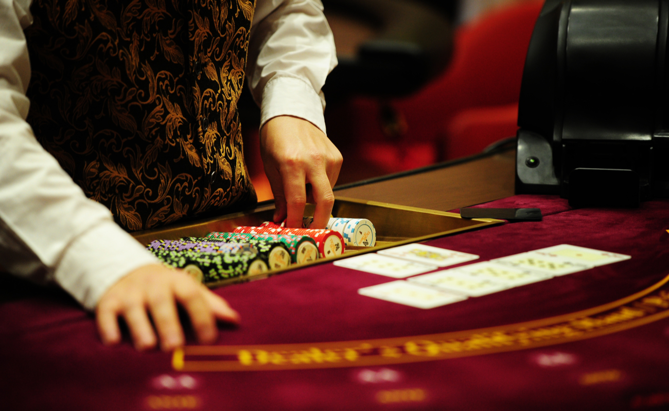 A dealer stands with chips, and playing cards at a red felt casino table.