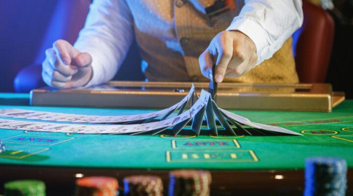 Professional croupier shuffling cards on a green felt casino table.