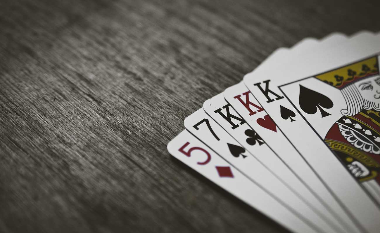 Playing cards laid out as a poker hand on a wooden grey table.
