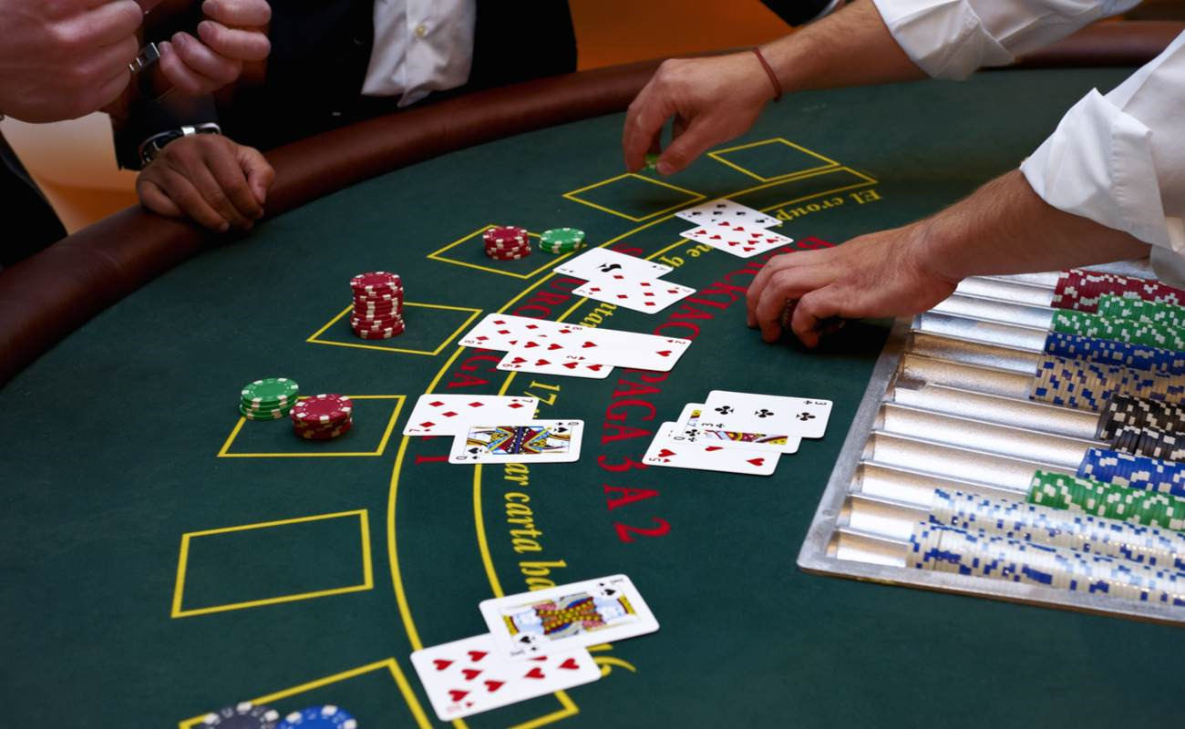 A close-up of a blackjack table with people playing.