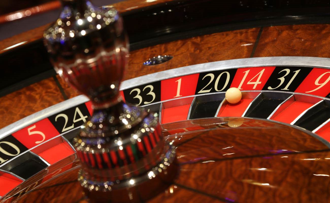 A roulette ball sits on red, number 14 on the roulette wheel.