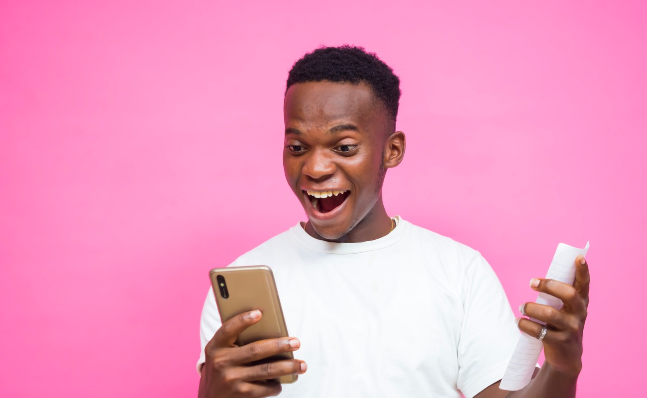 A young man feeling happy after winning a sports bet.