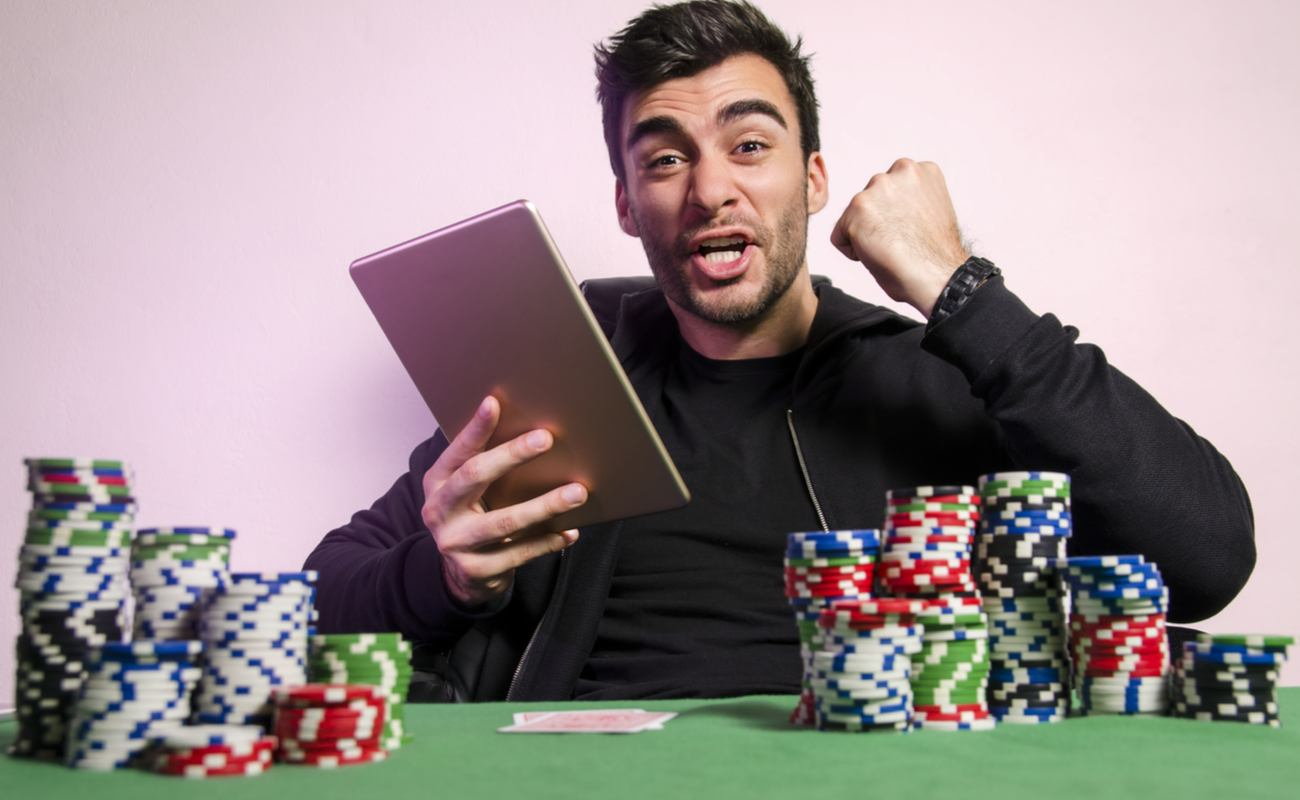 A young man celebrates his online slot win on his tablet, while sitting at a table with casino chips and playing cards.