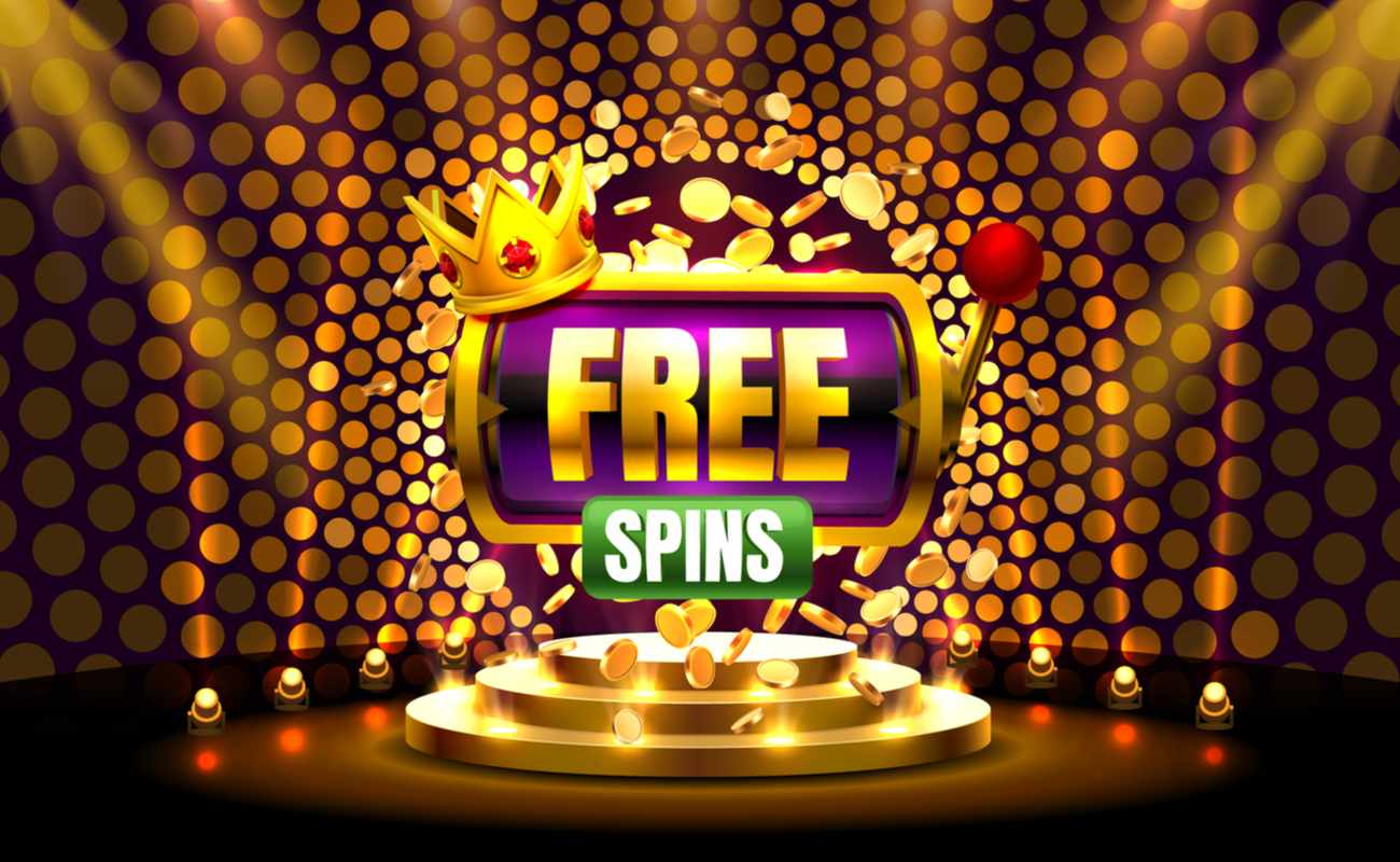 A 3D rendering of a slot machine with a crown and the words 'free spins' on it is seen sitting above a stage under spotlights.