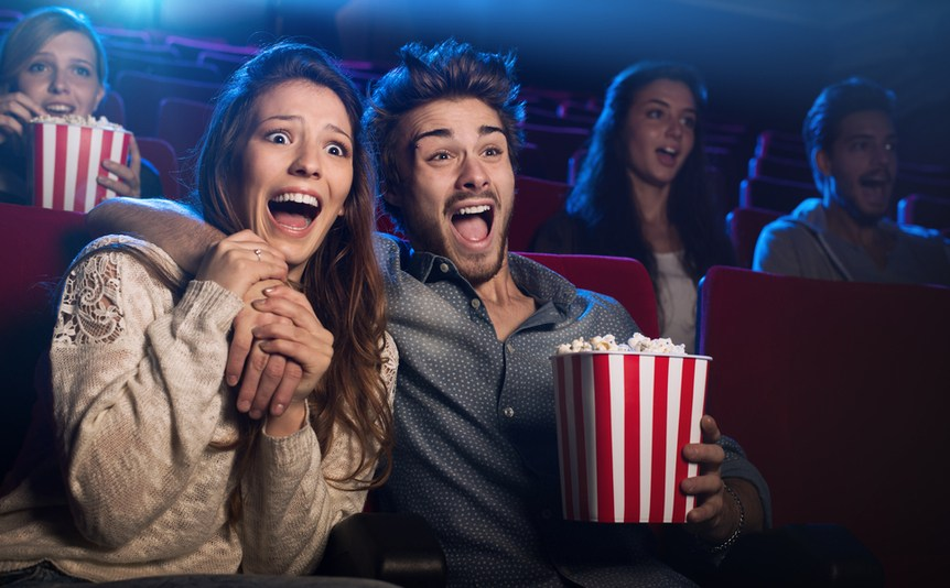 A young couple watch an exciting movie at the cinema.