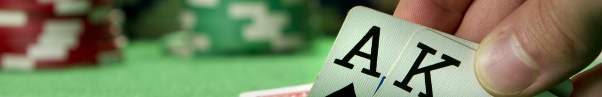 A poker player looks at the cards they've been dealt.