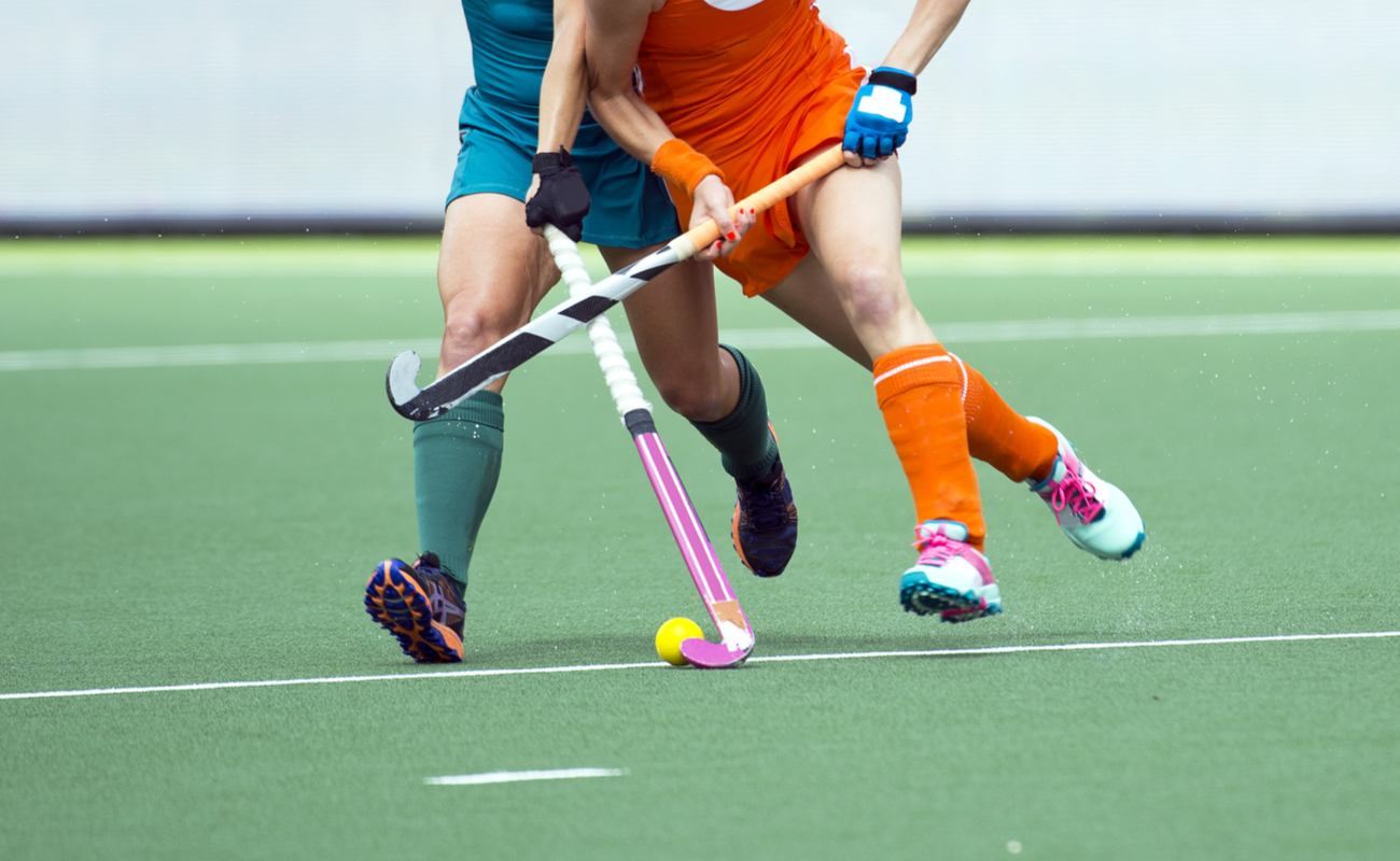 Two women playing a game of field hockey attempting to get the ball from each other.
