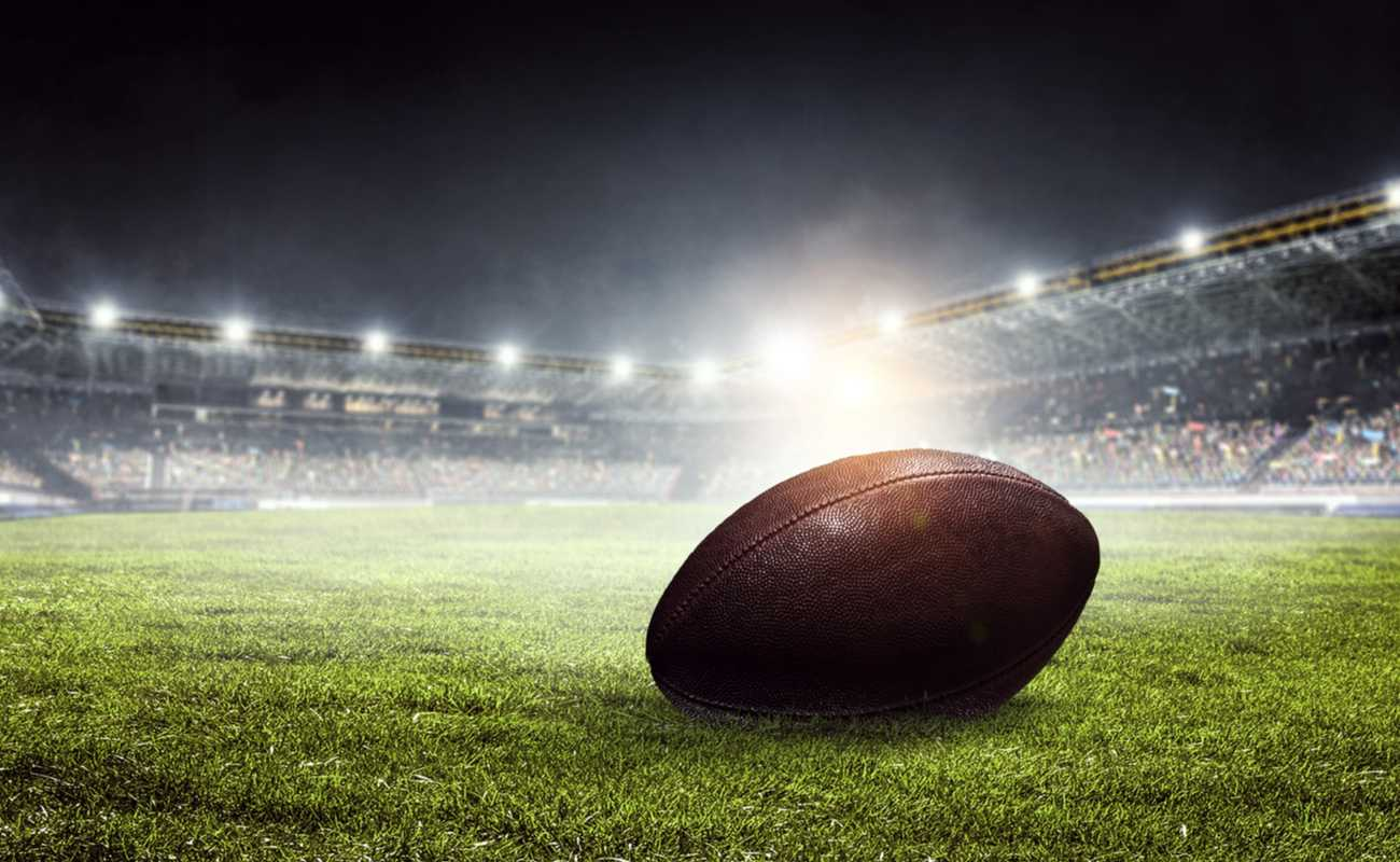 An American football lies on the field in a stadium.