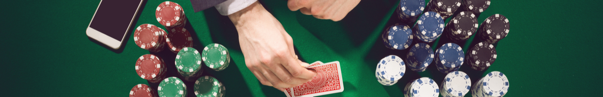 Man's hands holding playing cards at a green felt casino table with stacks of poker chips.
