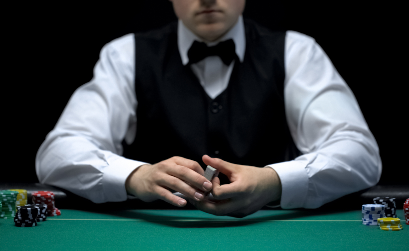 Professional croupier holding a pack of cards with stacks of poker chips on a green felt casino table.