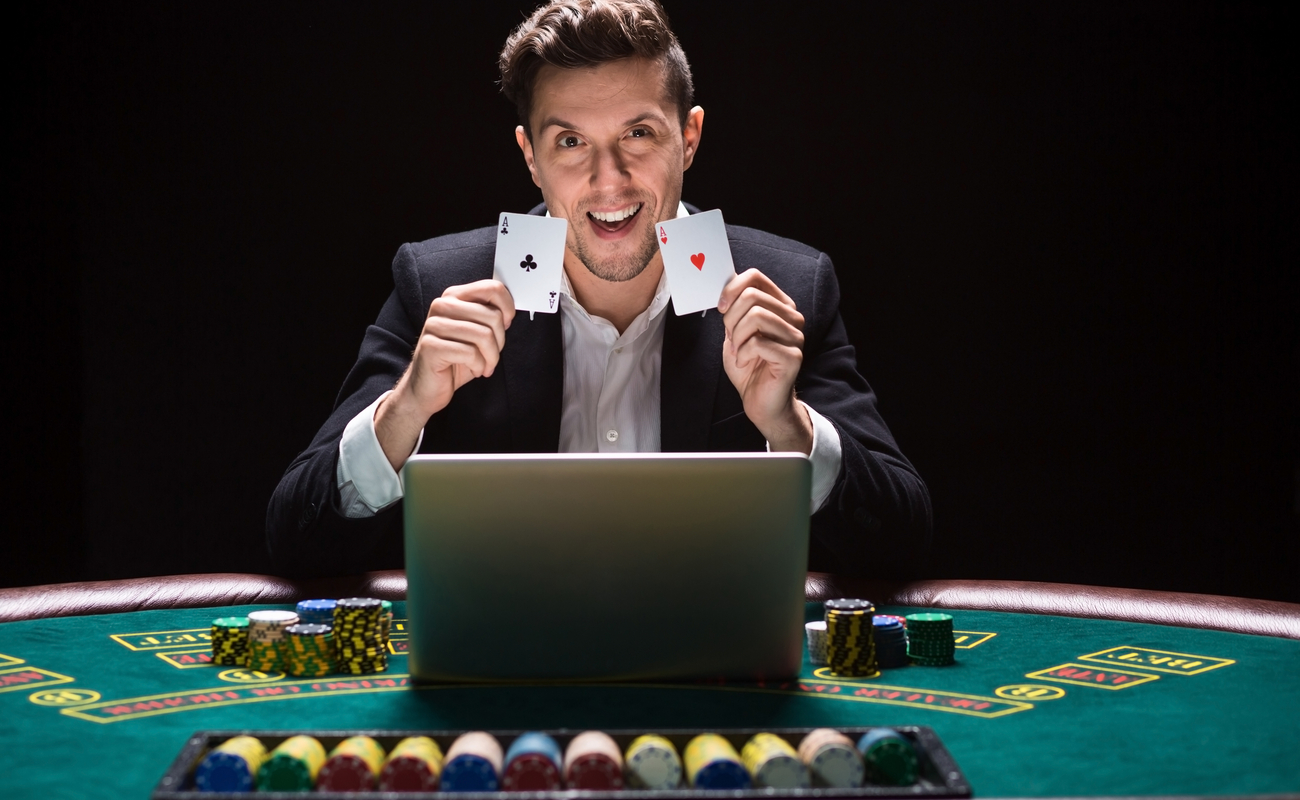 Online poker player holding playing cards and sitting at a casino table with his laptop and casino chips.