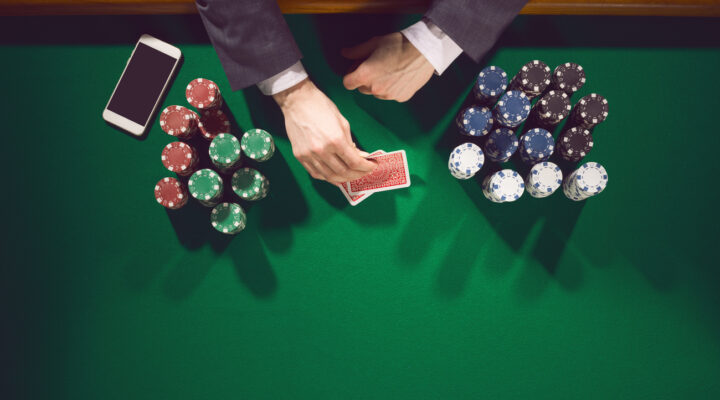 Poker player with hands and chips on the table