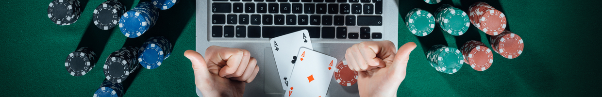 Man giving two thumbs up while playing online poker with casino chips all around.