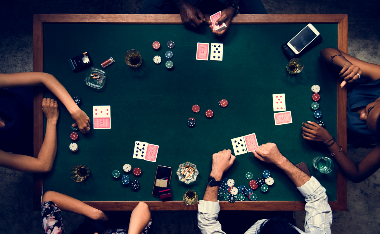 Aerial shot of five people playing poker with cards and chips at a casino table.