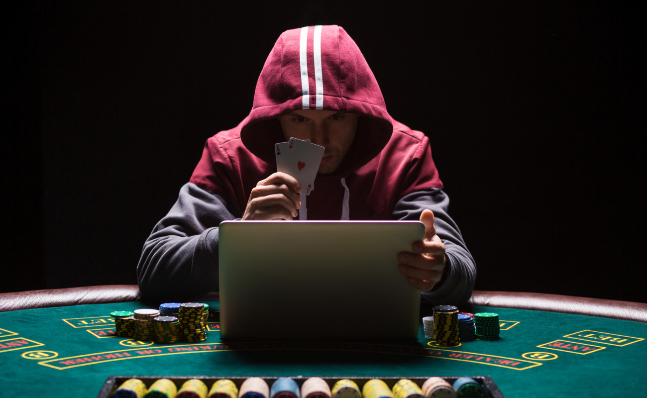 Online poker player sitting at a laptop on a casino table wearing a red hoodie and holding a pair of aces.