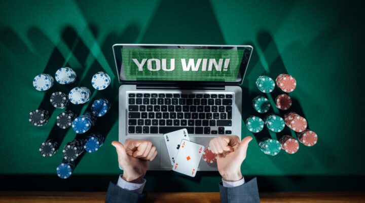 Man playing poker on a laptop showing two thumbs up