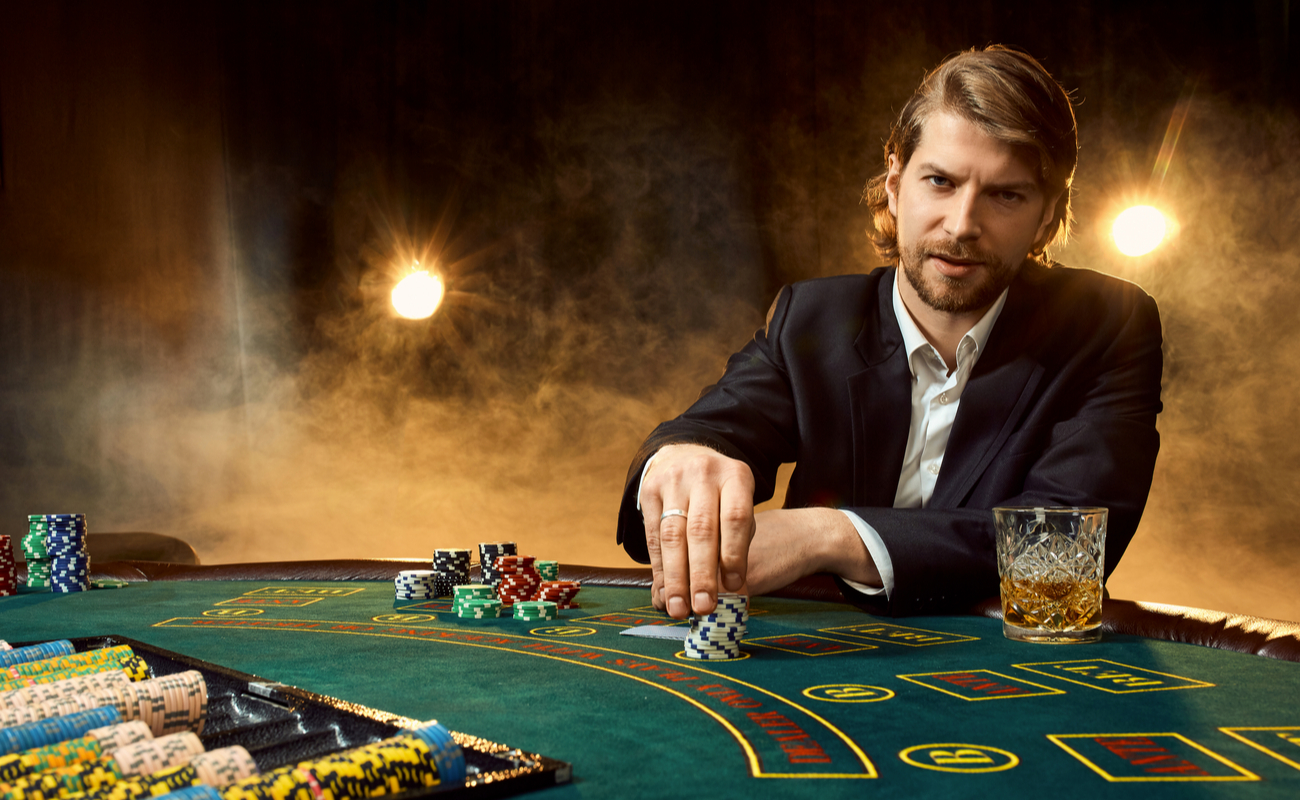 A man in a suit sitting at a poker table with stacks of casino chips.