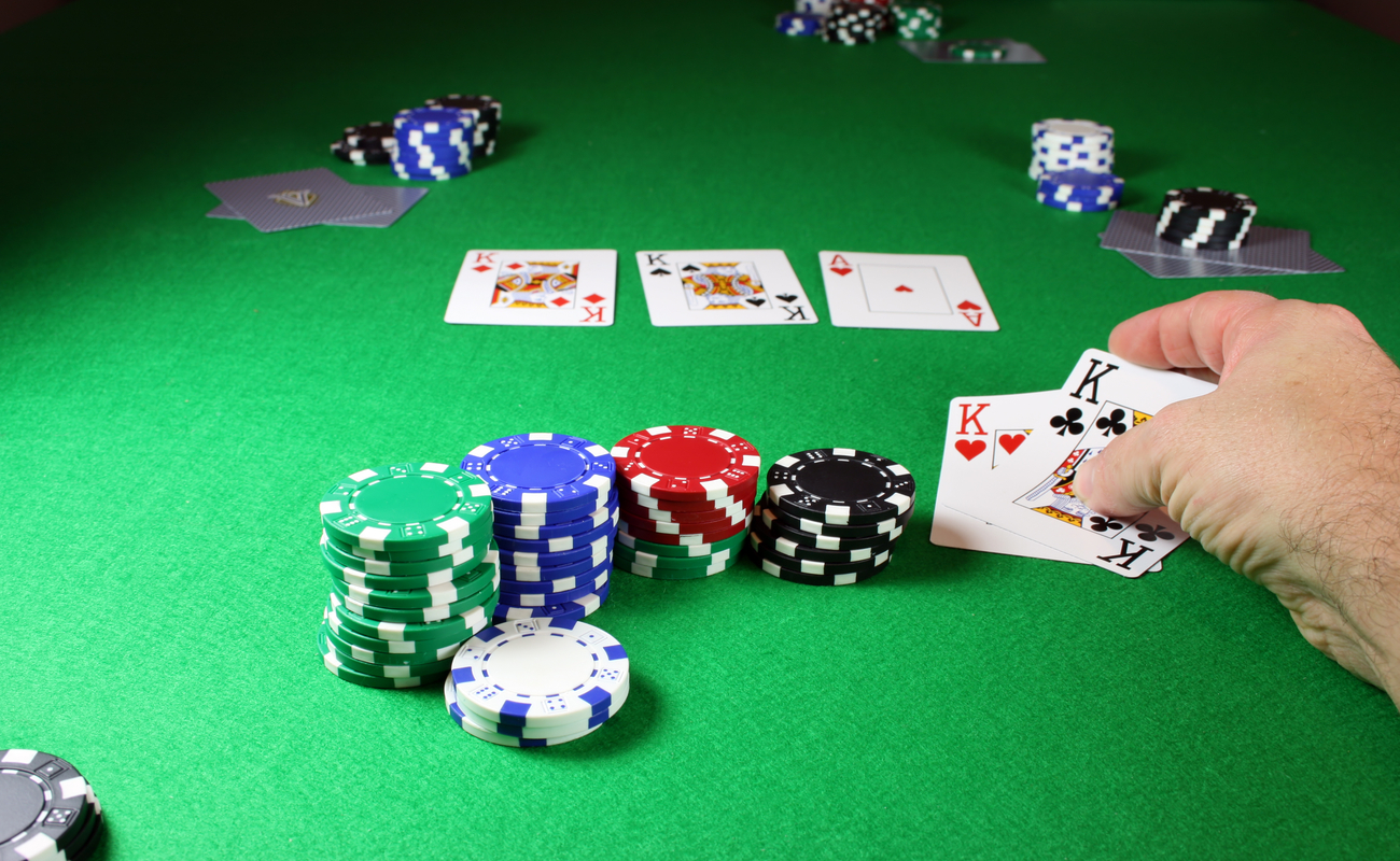 A player shows two kings next to some chips on a poker table.