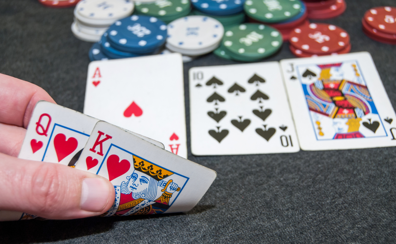 A hand reveals a king and queen, with other face-up playing cards in the background.