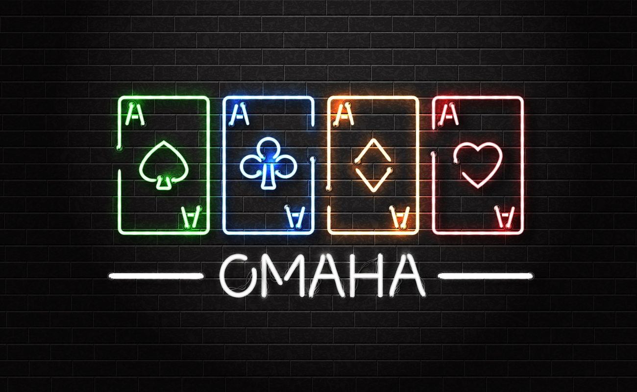 The word 'Omaha' and four aces lit up in neon lights on a wall.