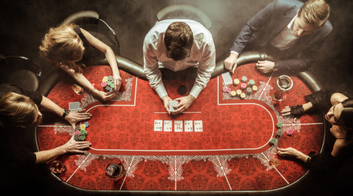 Players around a casino poker table with cards being dealt.